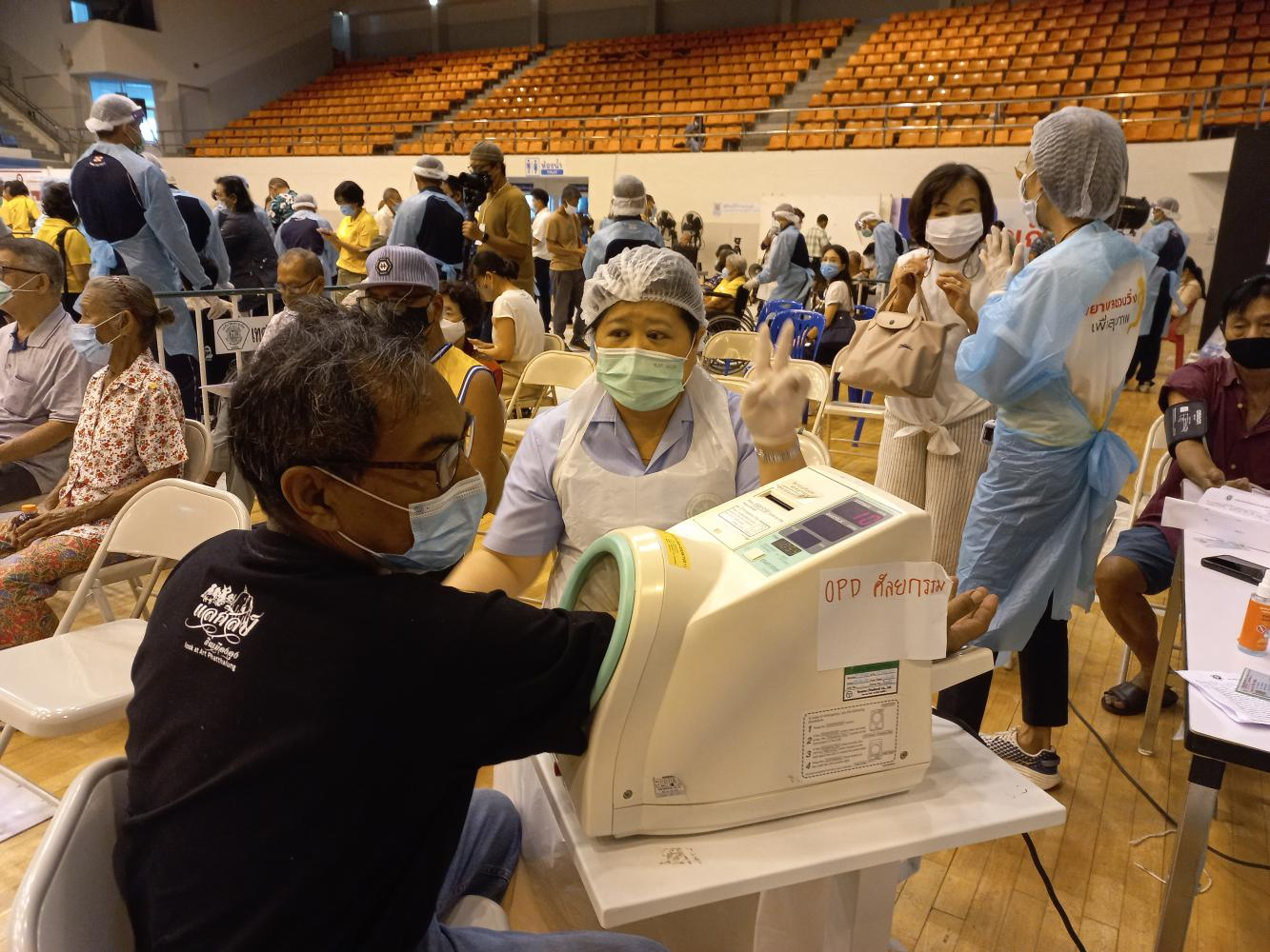 Elderly residents filled up an indoor sports stadium in Phuket on Monday as thousands rushed to receive Covid-19 vaccines. (Photo by Achadtaya Chuenniran)