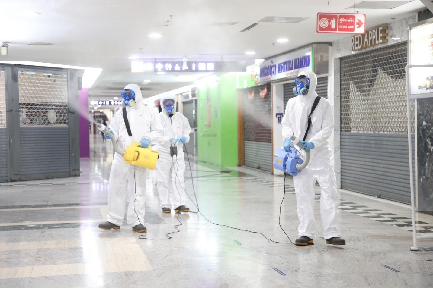Workers spray disinfectant inside MBK shopping centre which is helping tenants by charging them for water and electricity only.